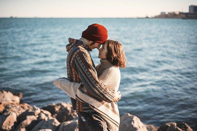 Ein junges Paar steht während der kalten Jahreszeit am Ufer des Meeres. Sie umarmen sich und schauen einander an.