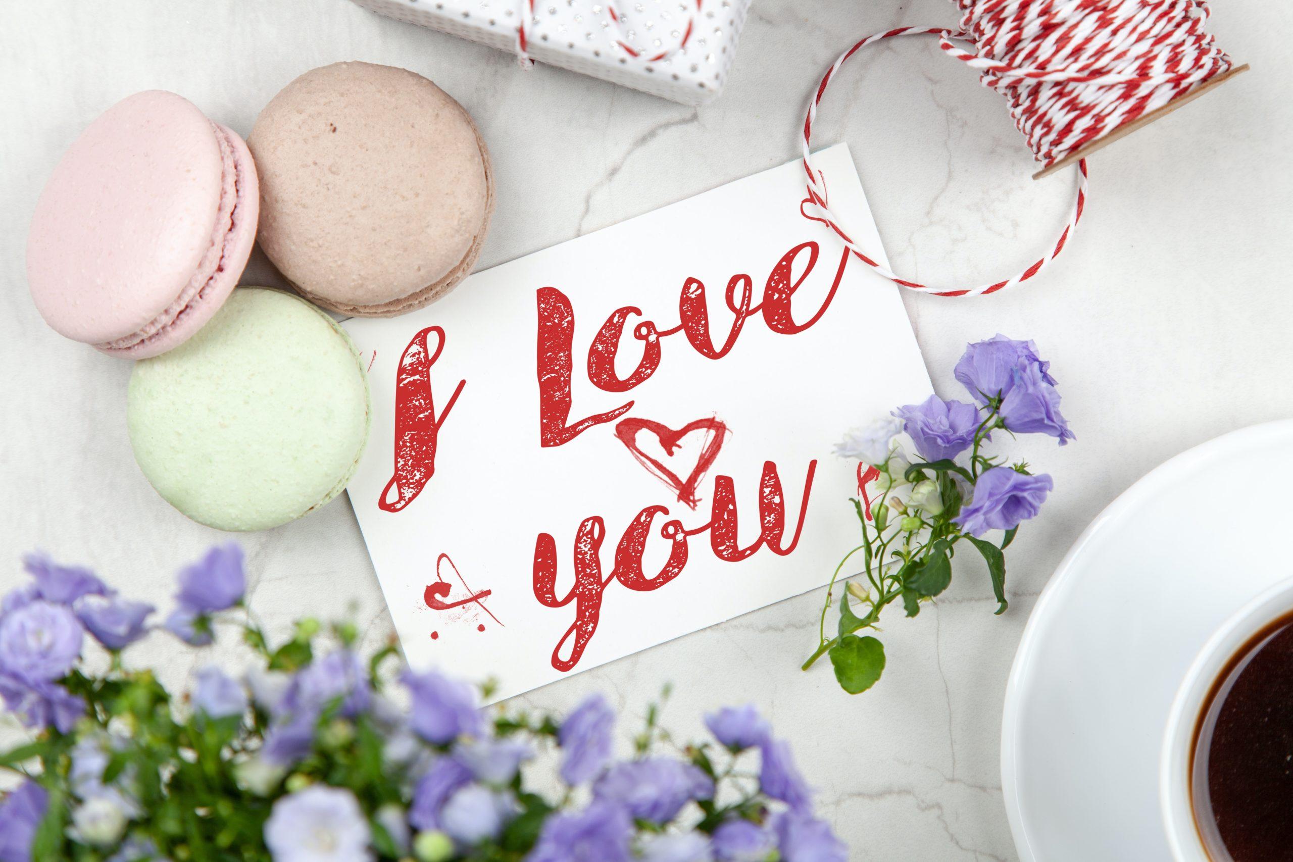 """Auf einer Karte steht """"I Love You"""" (Ich liebe dich). Neben der Karte liegen Kekse und es steht auch eine Kaffeetasse und ein Blumenstrauß daneben."""