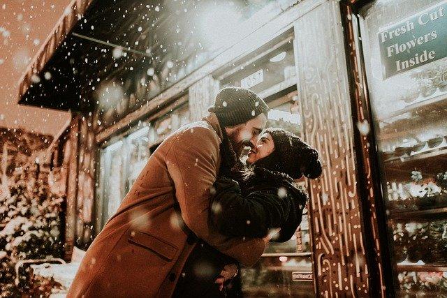 Ein junges Paar küsst sich. Es ist Winter und der Schnee rieselt langsam herunter.