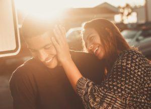 Junges Paar im Sonnenschein. Die Frau berührt zärtlich das Gesicht des Mannes.