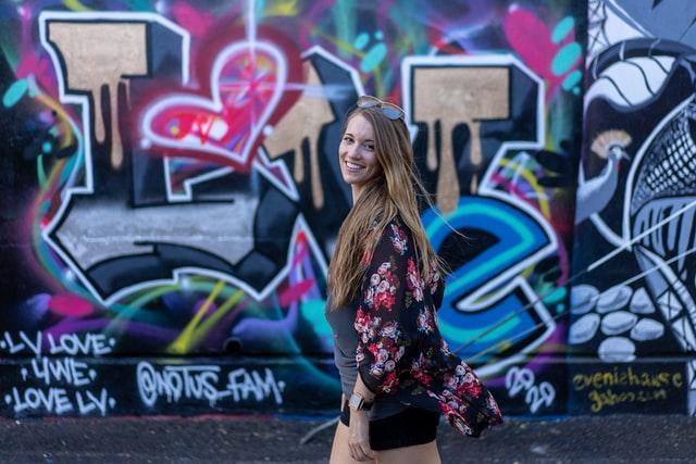 Eine junge Frau läuft an einer Graffiti Wand vorbei, auf der I Love You steht
