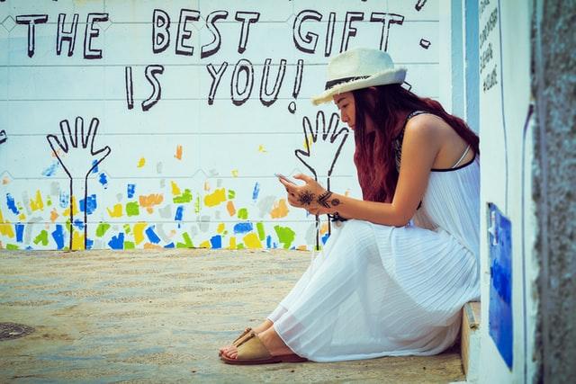 """Eine junge Frau sitzt auf einer Stufe und schaut auf ihr Handy. Im Hintergrund ist """"The best gift is you!"""" (Das beste Geschenk bist du) auf eine Wand geschrieben"""