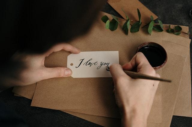 """Jemand schreibt mit einem Tintenfüller auf eine kleine Karte """"I love you"""""""