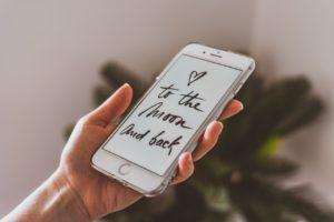 """Auf einem Handy steht """"I love you to the moon and back"""" (Ich liebe dich bis zum Mond und zurück)"""