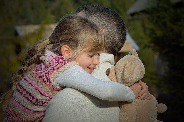 Mädchen umarmt liebevoll ihren Papa und hat dabei ihren Teddy im Arm