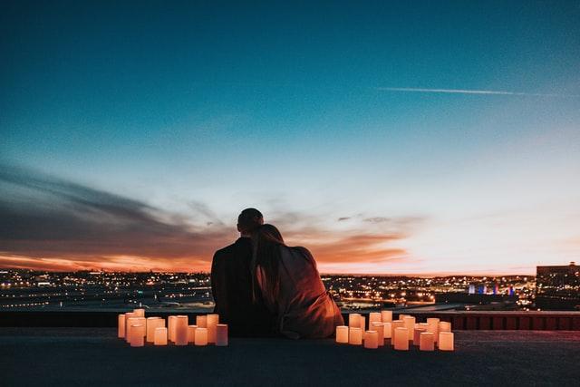 Ein junges Paar lehnt sich aneinander an und schaut auf die Lichter einer Stadt. Es ist Abenddämmerung und neben sich haben sie viele Kerzen aufgestellt.