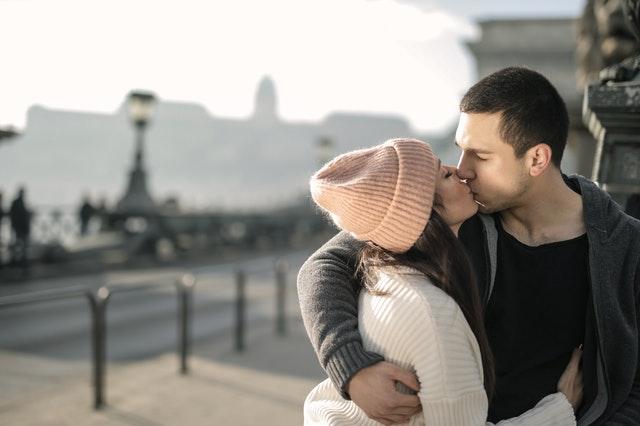 Ein junges Paar küsst sich vor einer Stadtkulisse.